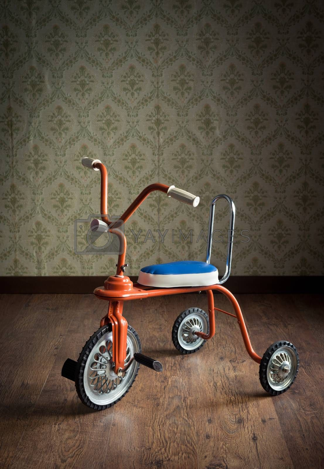 Vintage orange tricycle on hardwood floor and vintage wallpaper on background.