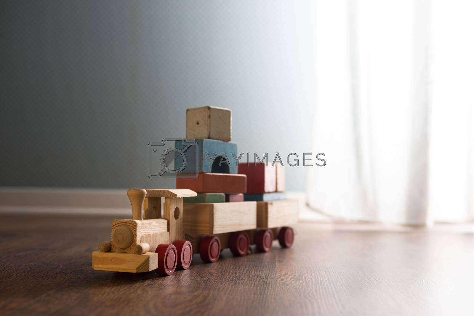 Vintage wooden toy train next to a window on hardwood floor.