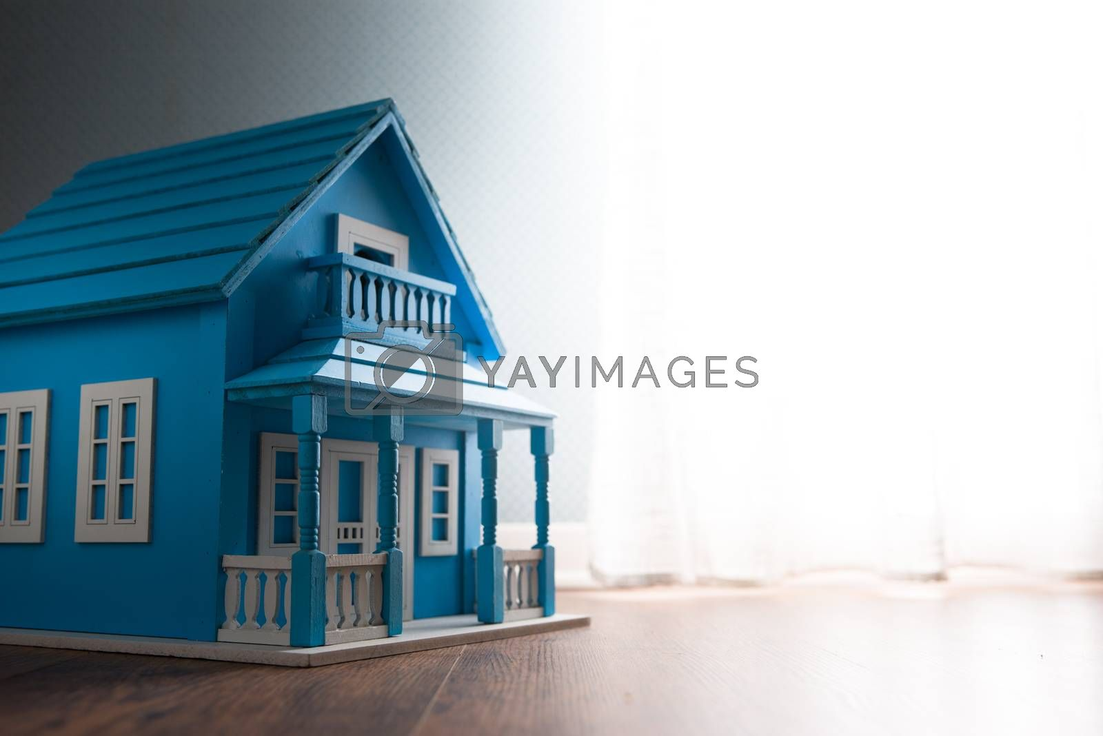 Blue wooden model house next to a window with curtain on wooden floor.