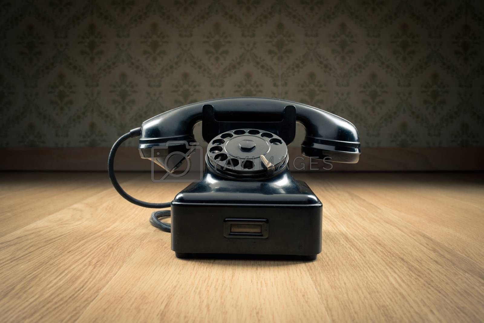 Black 1950s style phone on hardwood floor and vintage wallpaper on background.