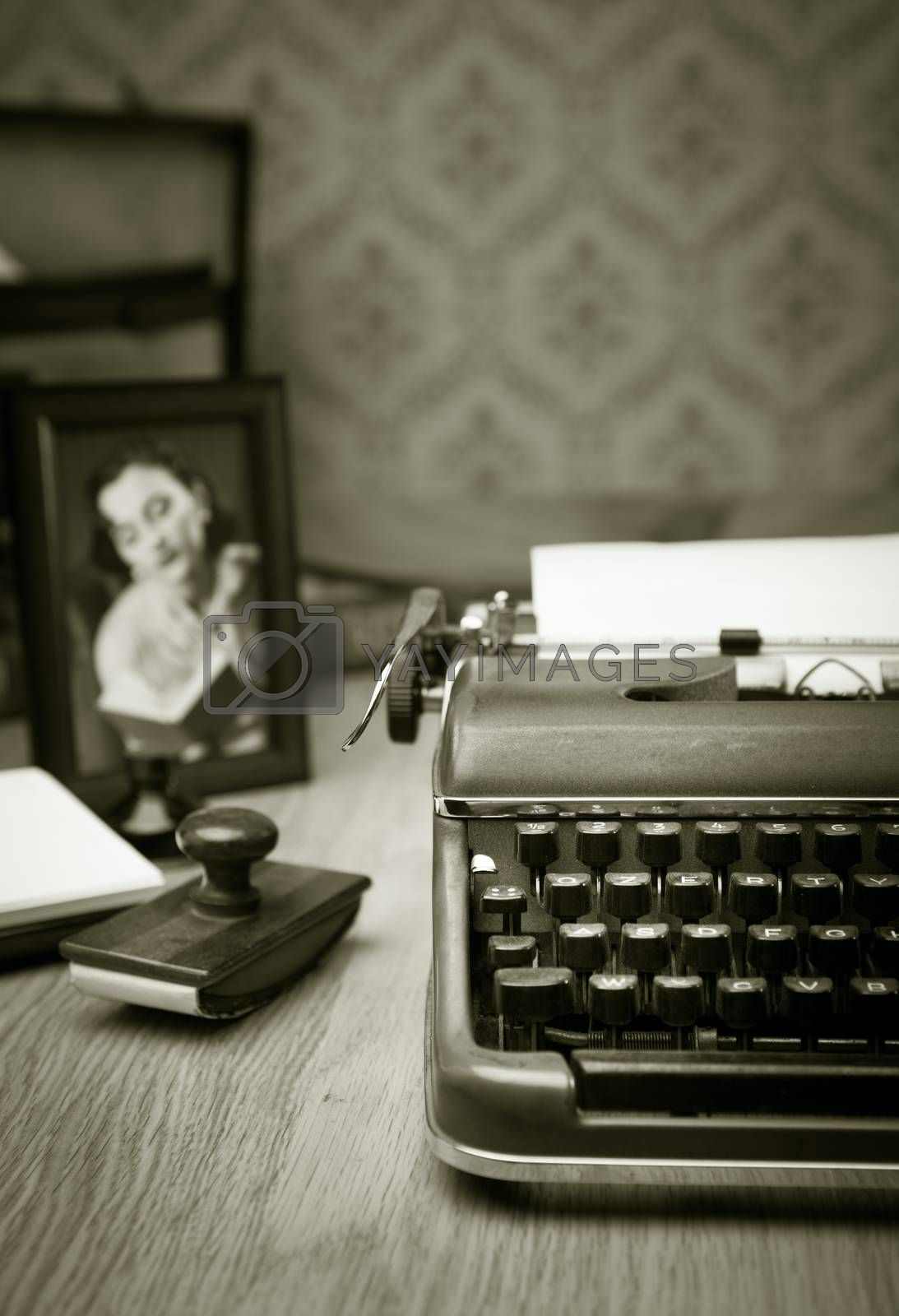 Vintage typewriter on a wooden desk with old frame and picture on background.