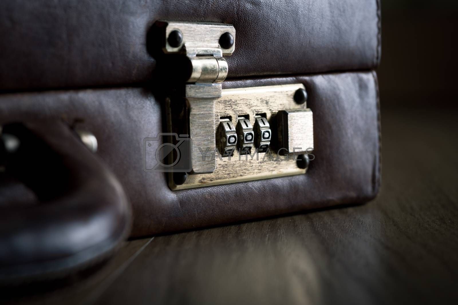 Leather briefcase lock and handle close-up on dark hardwood floor.