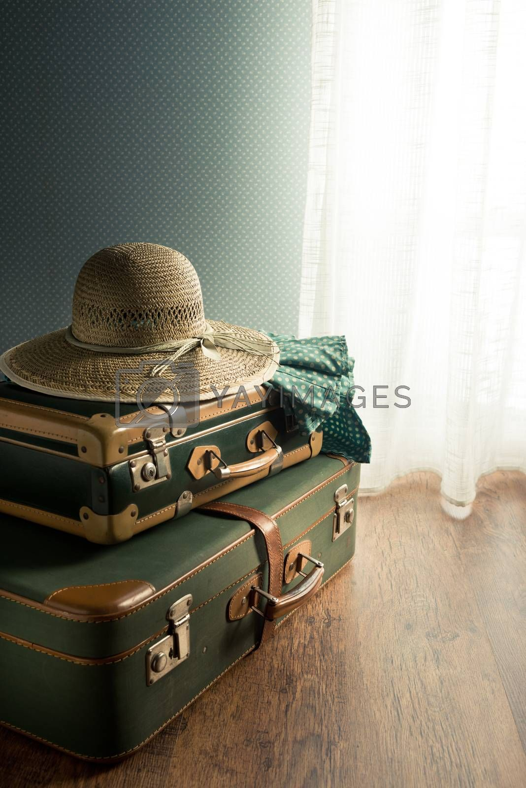 Vintage suitcase with straw hat on the floor next to a window.