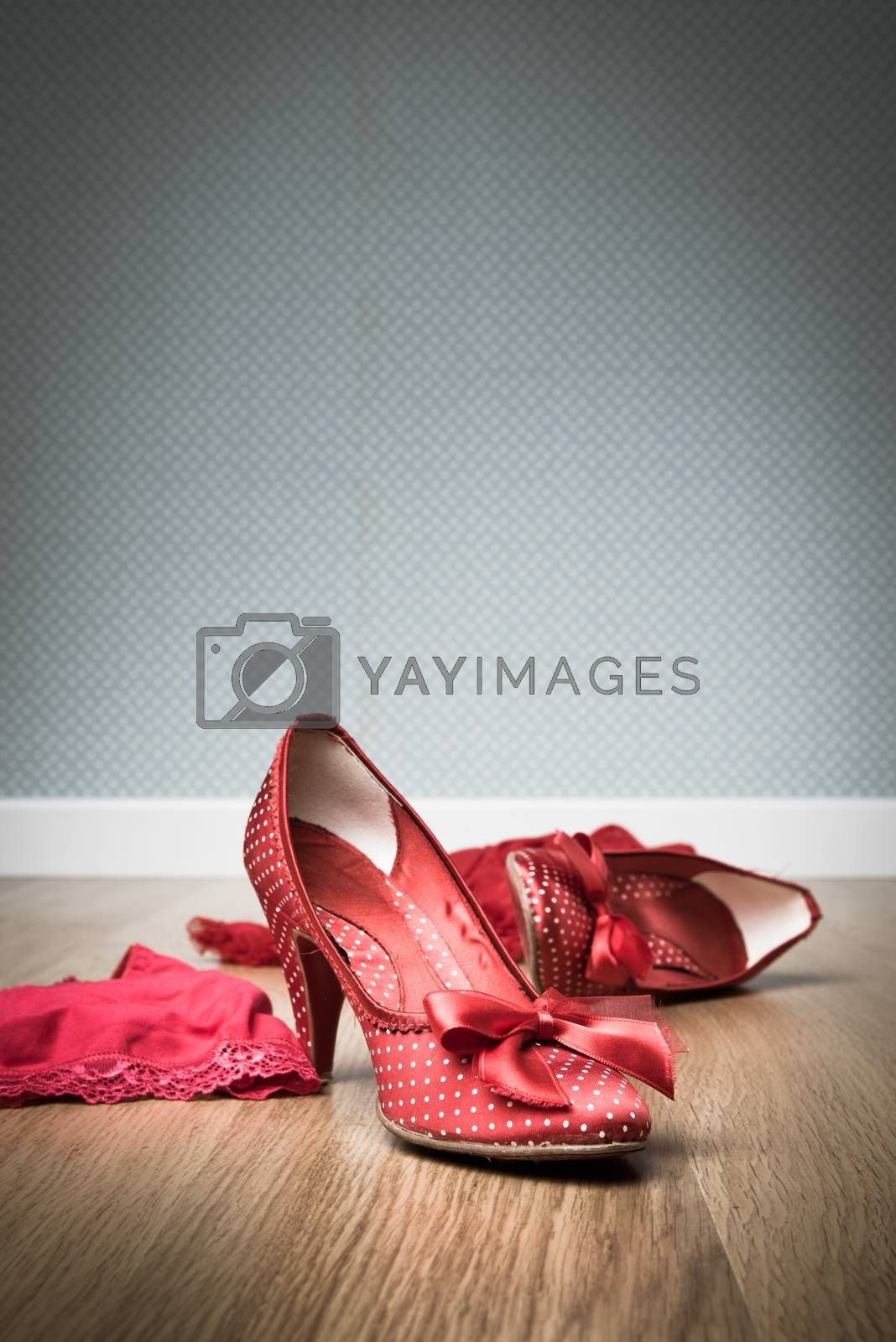 Female red shoes and lingerie on floor, sensuality and seduction concept.
