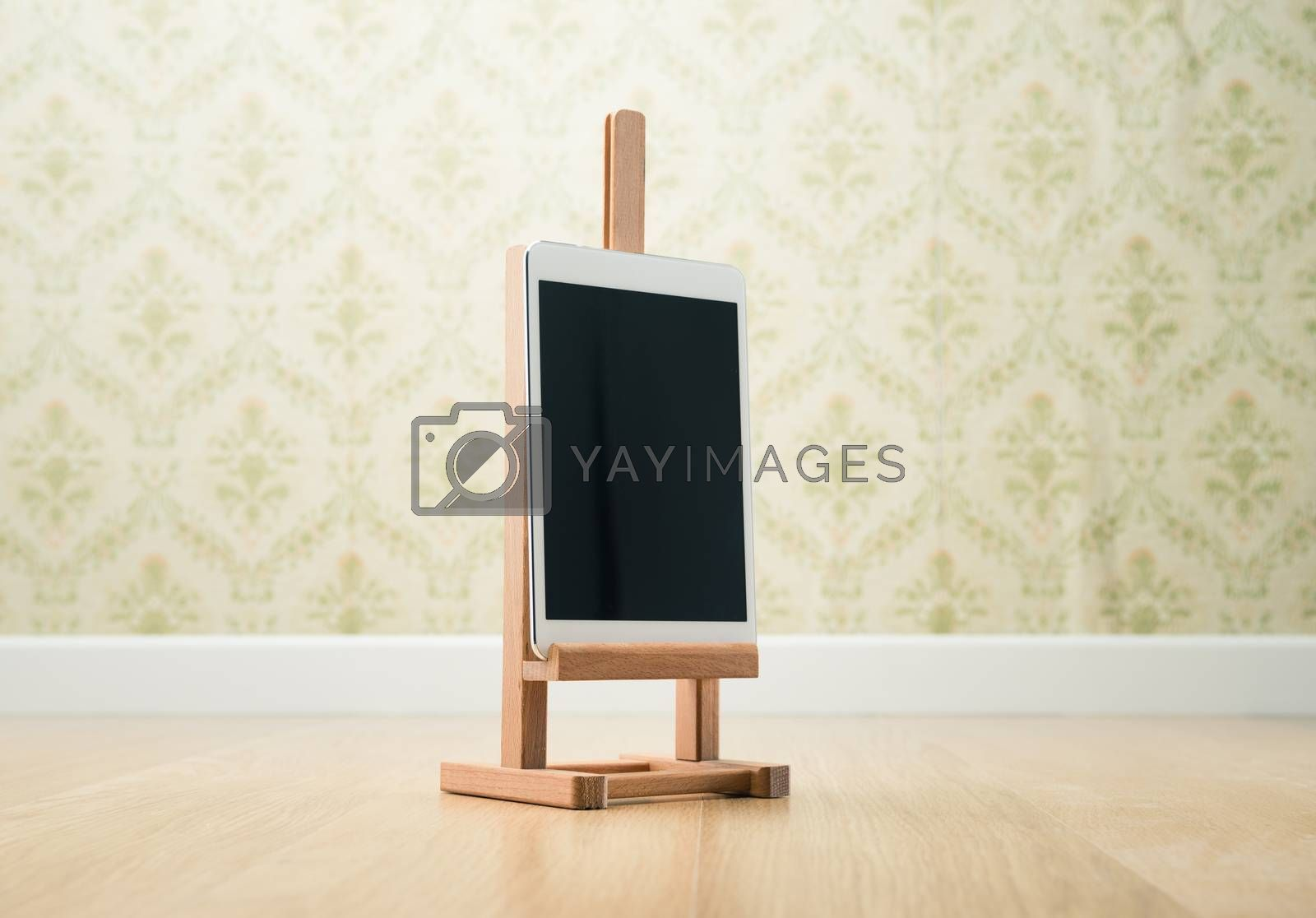 Digital tablet on wooden painting easel, vintage wallpaper on background.