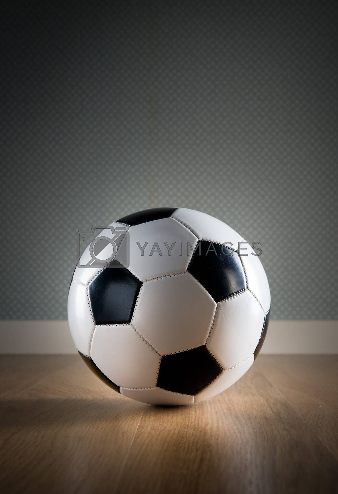Soccer ball on hardwood floor and vintage wallpaper on background.