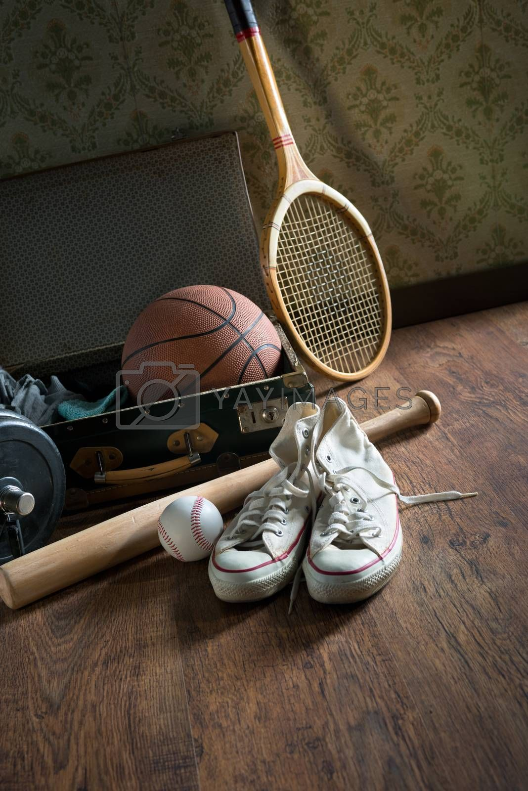 Vintage suitcase with sports equipment on wooden floor with canvas shoes on foreground.