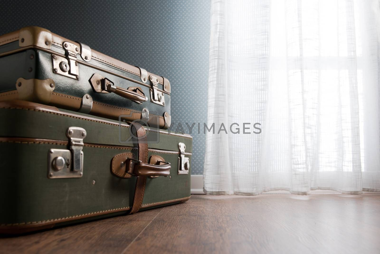 Pile of vintage suitcases next to a window on hardwood floor.