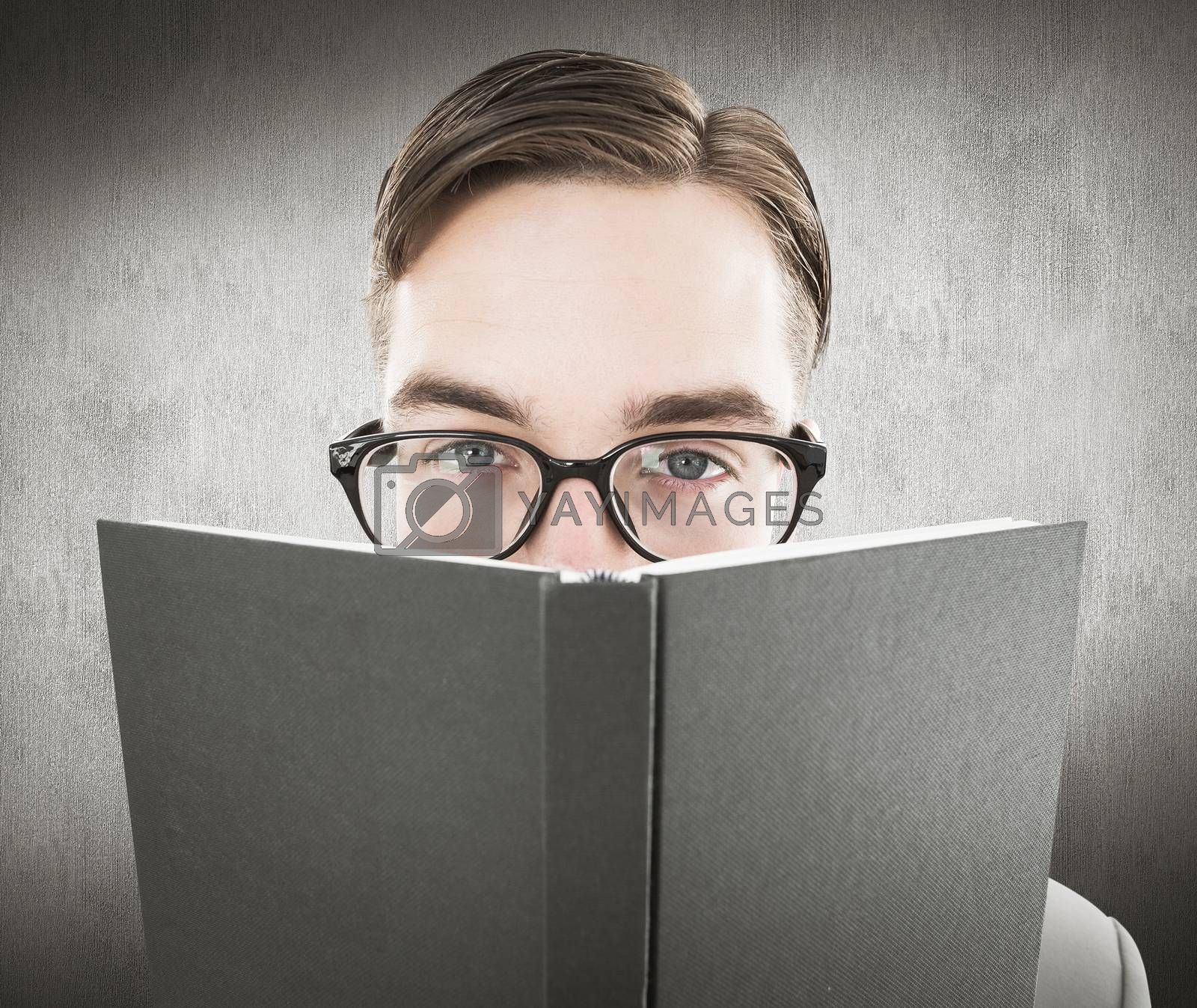 Geeky man looking over book against white and grey background