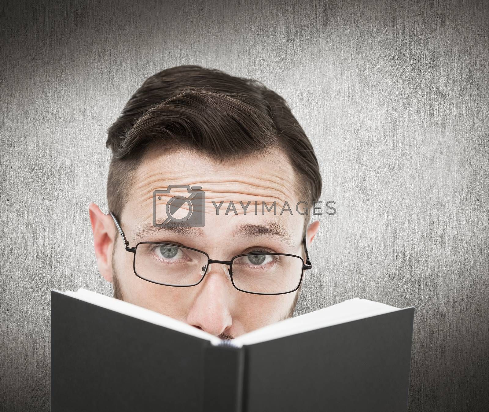 Young geek looking over black book against white and grey background