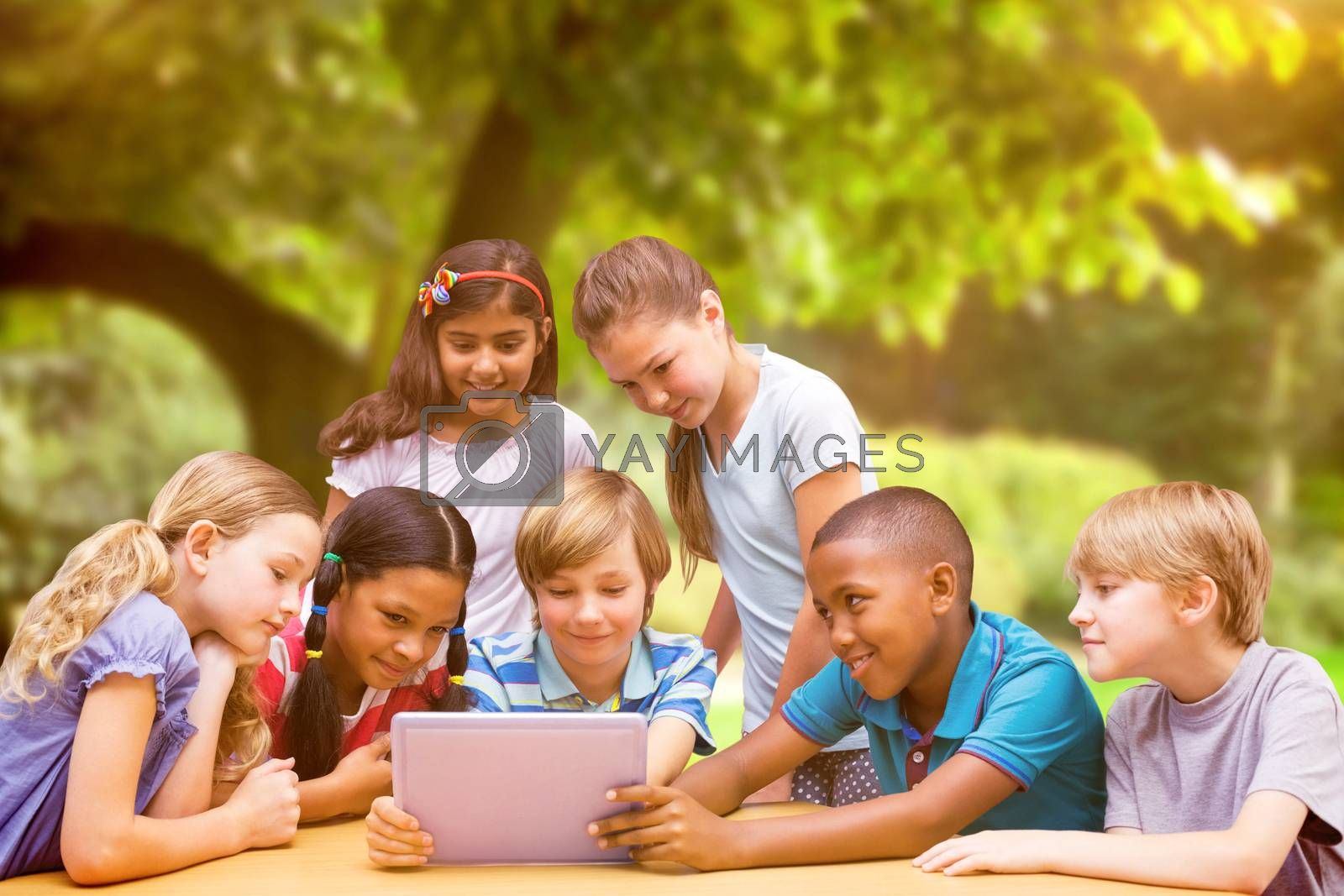 Cute pupils using tablet computer in library  against trees and meadow in the park