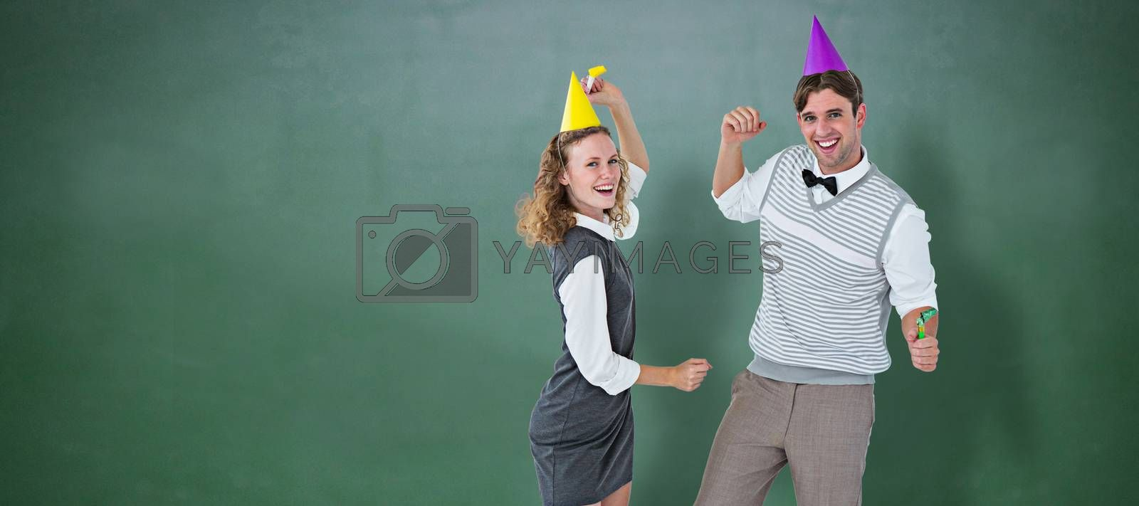 Geeky couple dancing with party hat  against green chalkboard