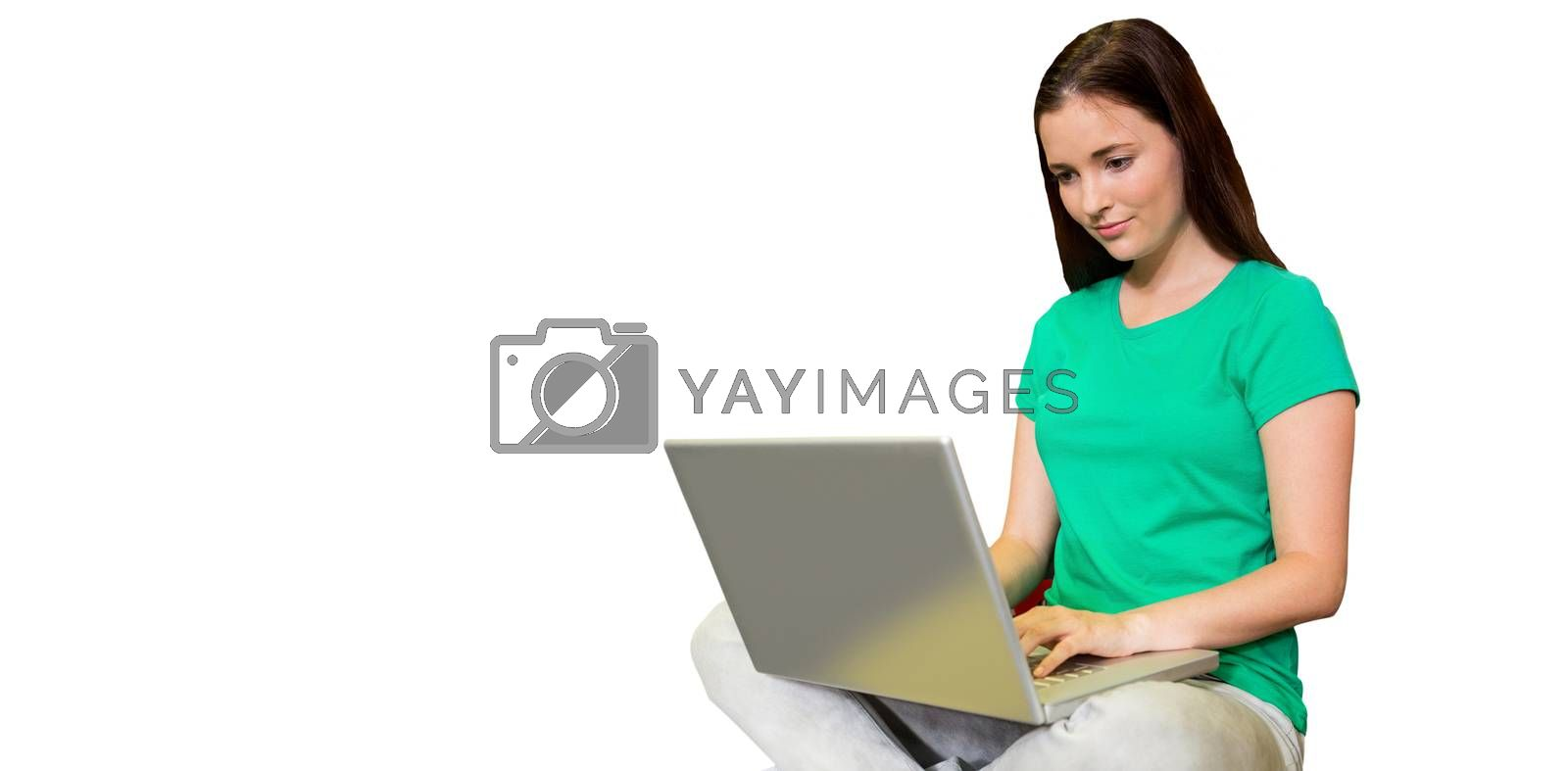 Student sitting on floor in library using laptop  against white background with vignette