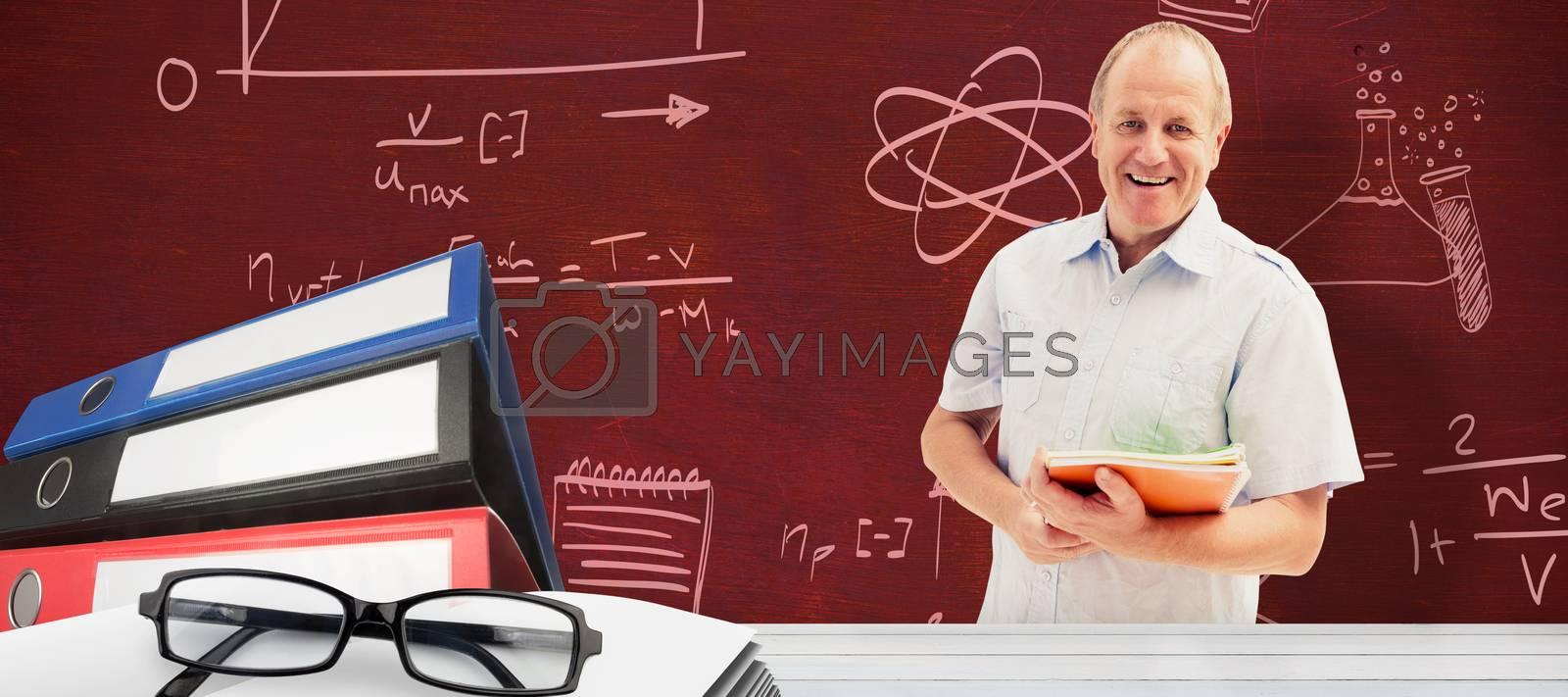 Mature student holding notebooks against desk