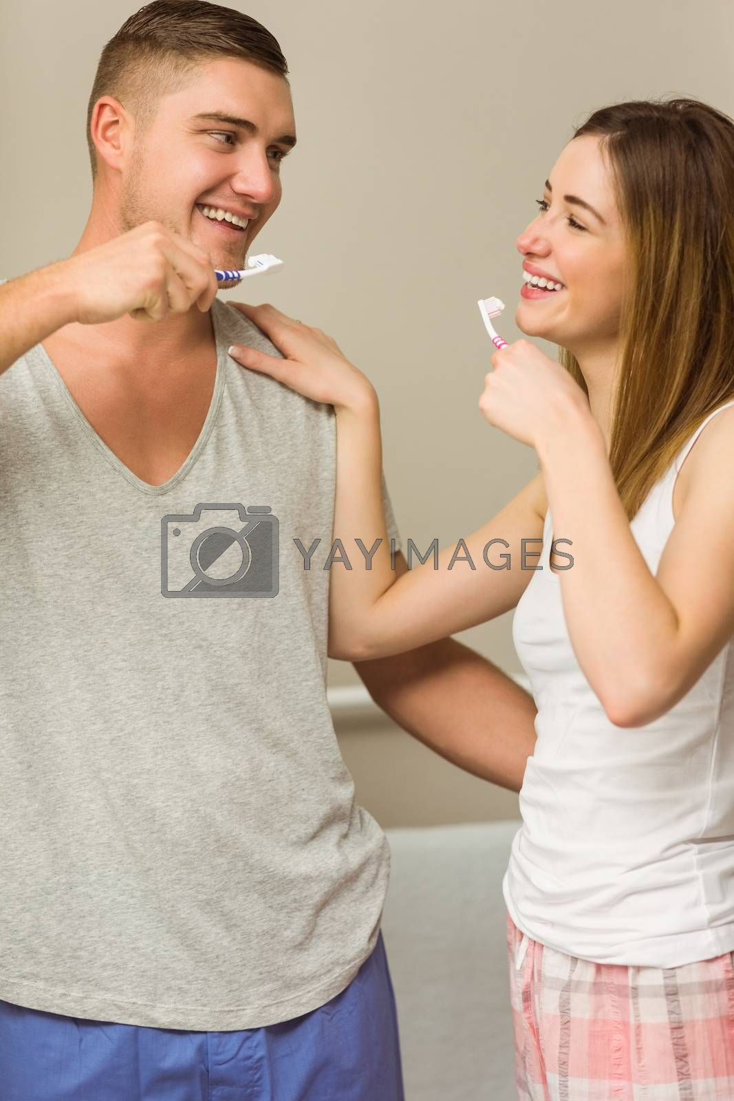 Cute couple brushing their teeth at home in the bathroom