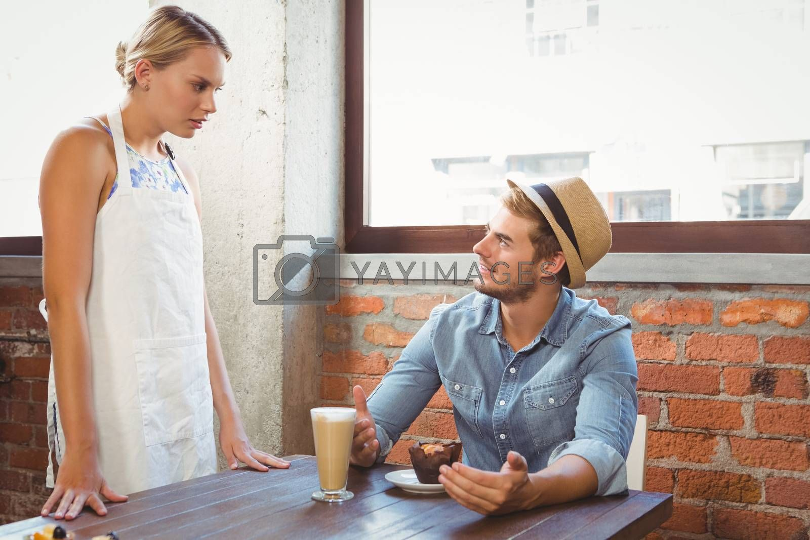 Handsome hipster talking to blonde waitress at coffee shop