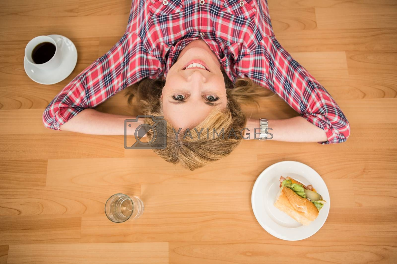 Portrait of smiling woman lying on floor surrounded by food and drink