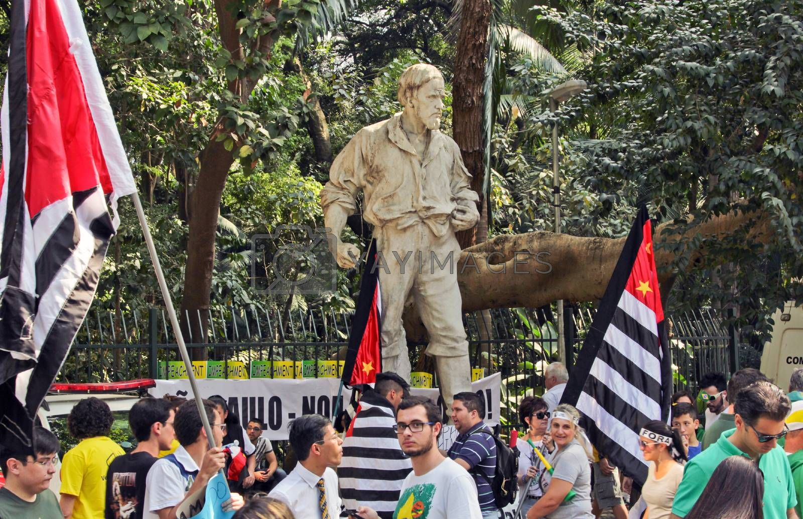 SAO PAULO, BRAZIL August 16, 2015: An unidentified group of people with flags in front of Bartolomeu Bueno da Silva statue in  the protest against federal government corruption in Sao Paulo Brazil.