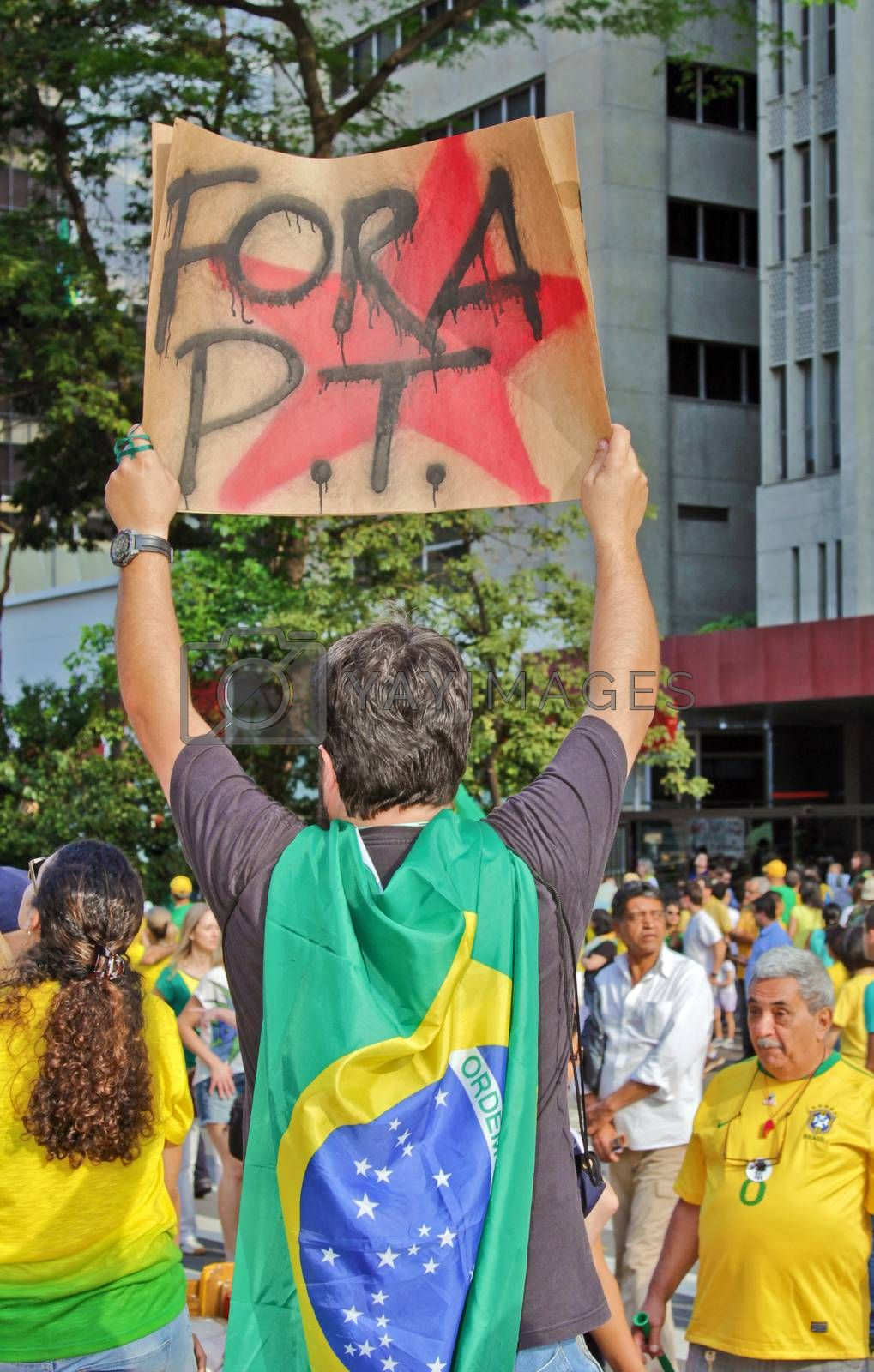 SAO PAULO, BRAZIL August 16, 2015: An unidentified man with a flag and a poster in the protest against federal government corruption in Sao Paulo Brazil.