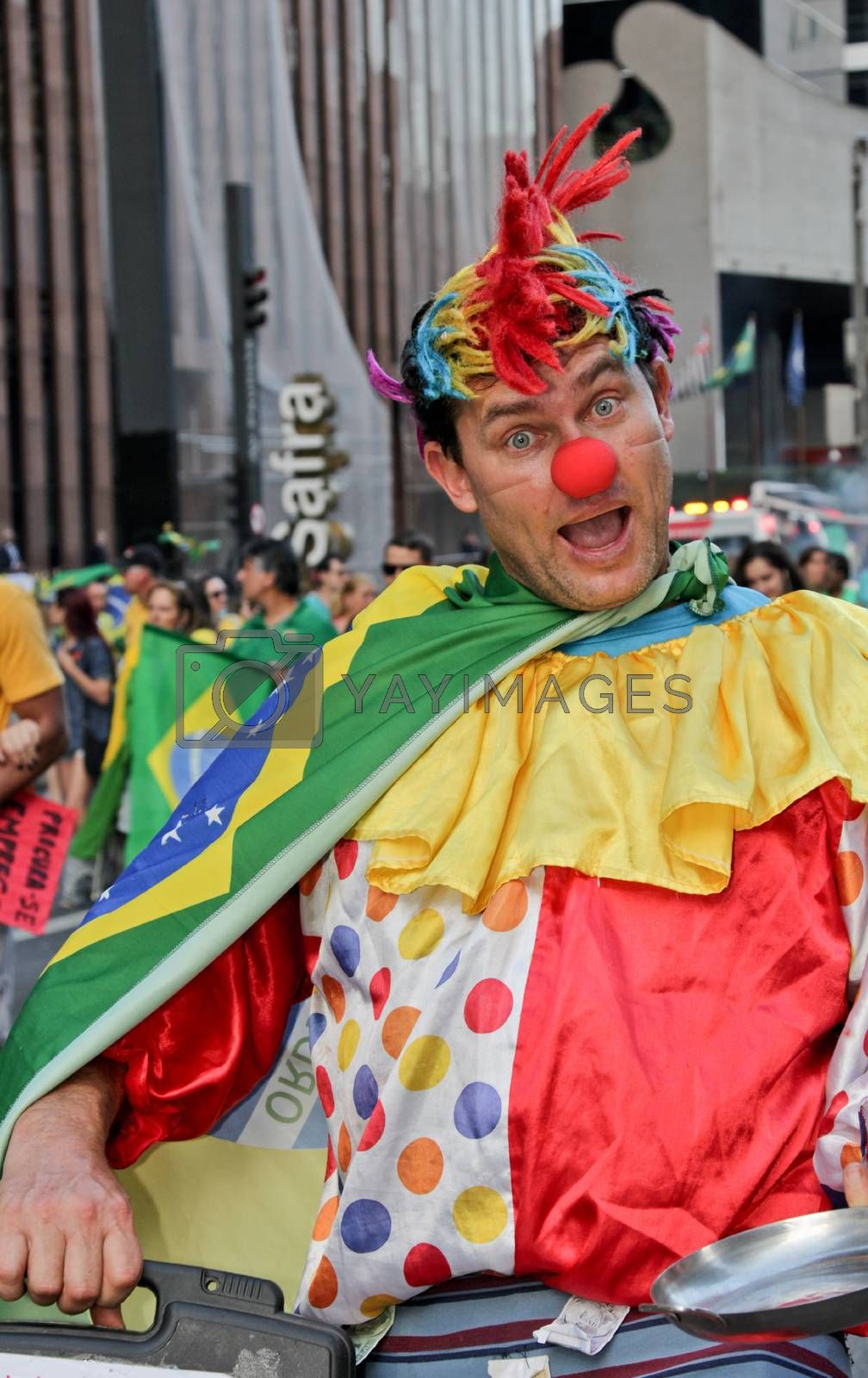 SAO PAULO, BRAZIL August 16, 2015: An unidentified man with clown costume in the protest against federal government corruption in Sao Paulo Brazil. Protesters call for the impeachment of President Dilma Rousseff.
