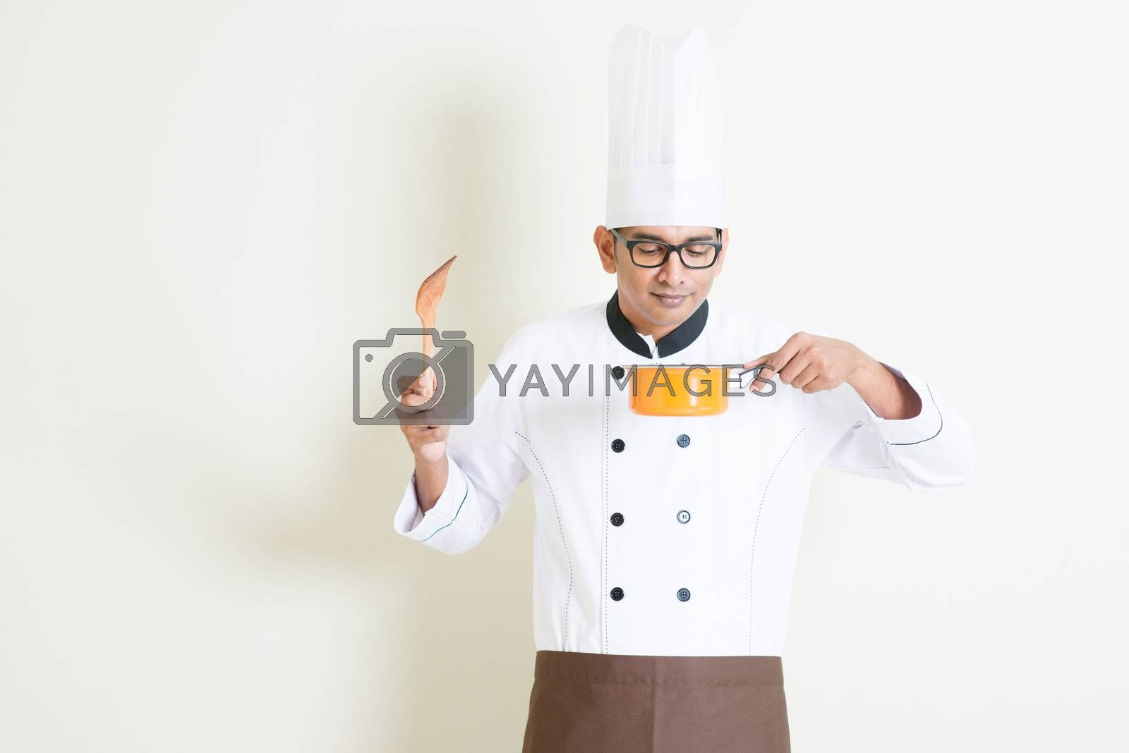 Indian male chef in uniform cooking and enjoy the food aroma by szefei
