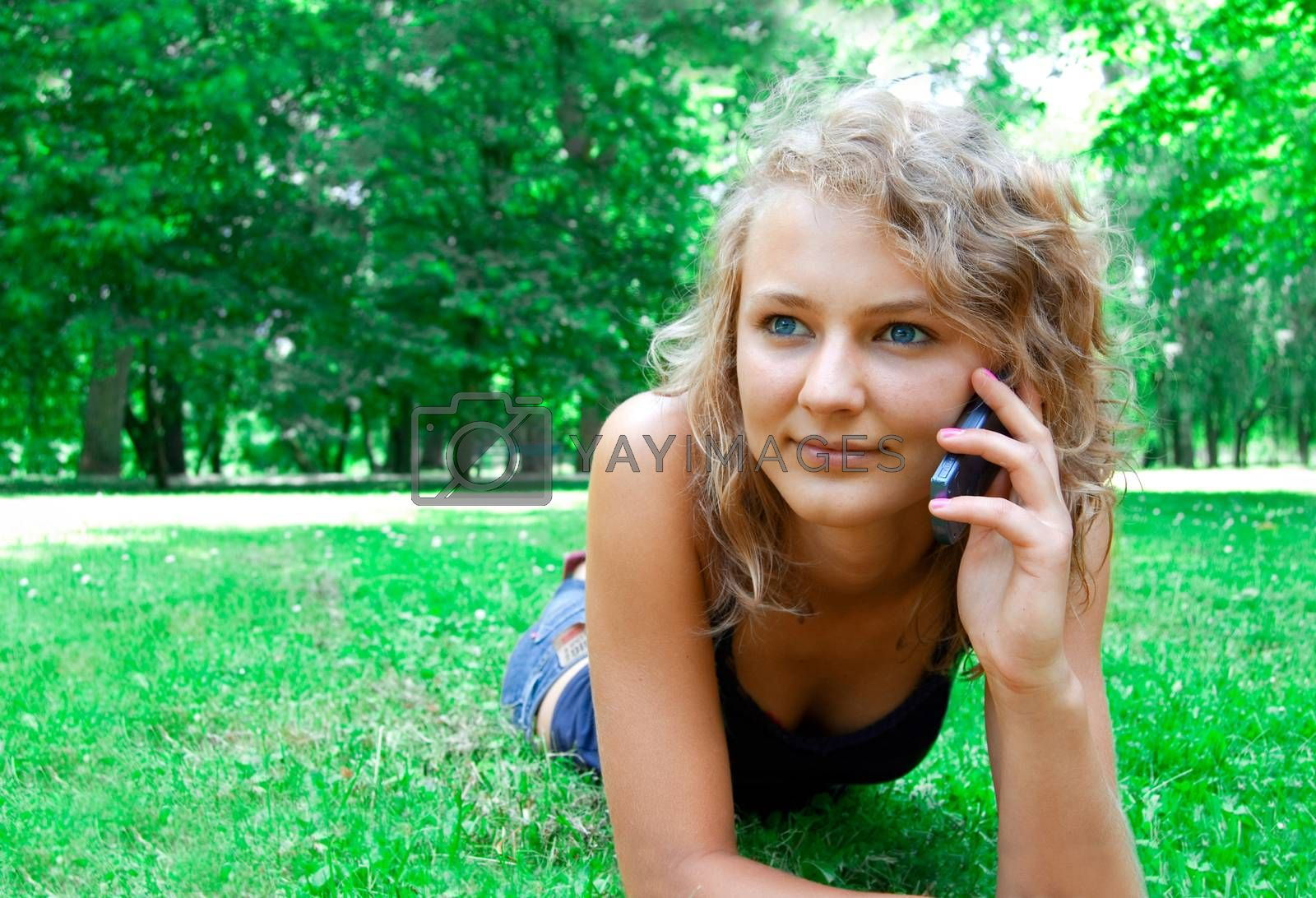 Communication conceptual image. Young beautiful girl talking on a cell phone.