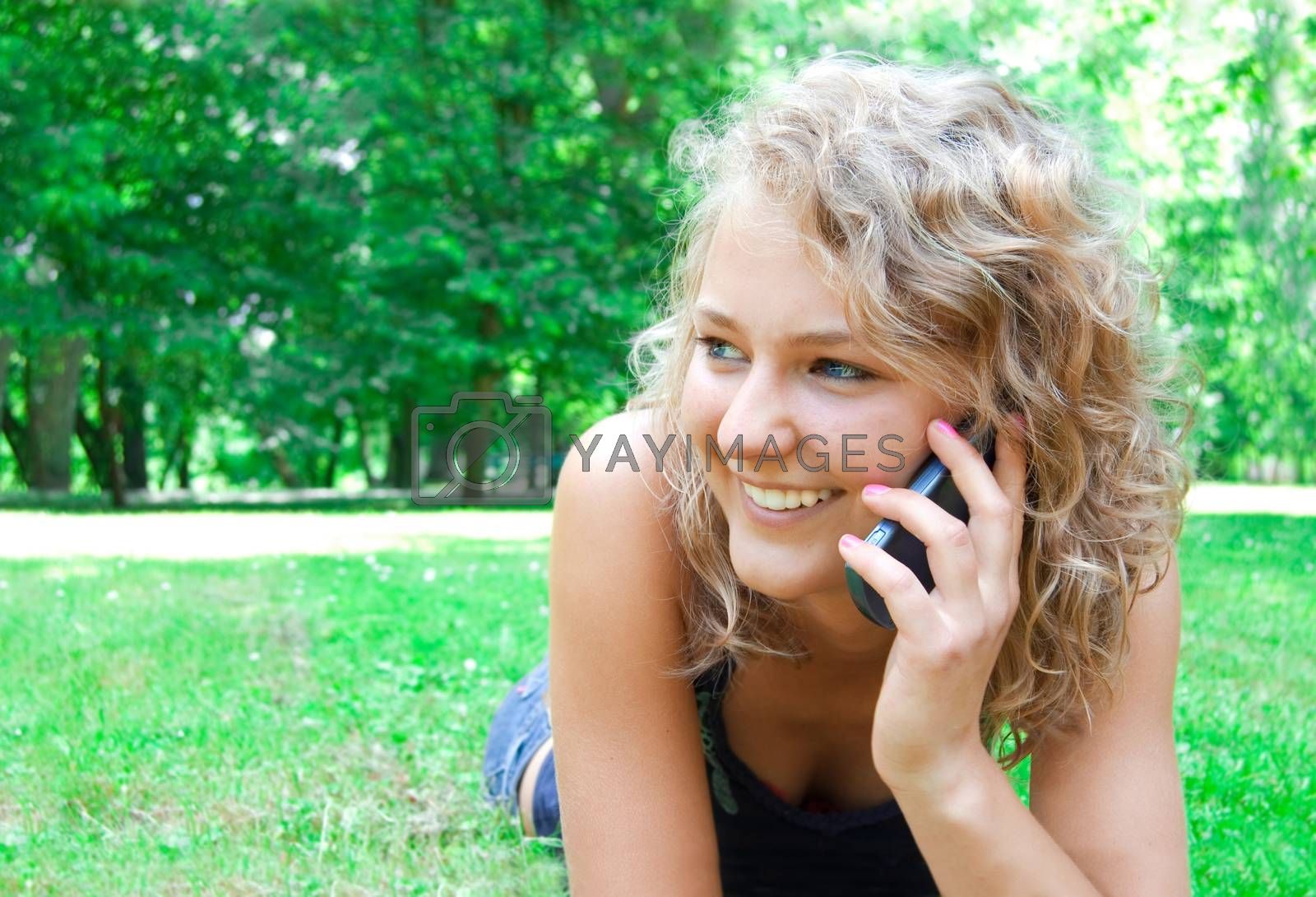 Communication conceptual image. Young beautiful girl talking on a cell phone and smiles.