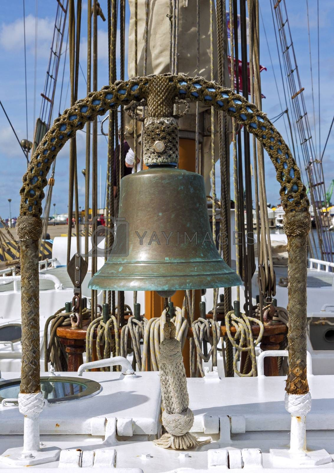 Closeup of ship deck with sail ropes and old bell made of copper