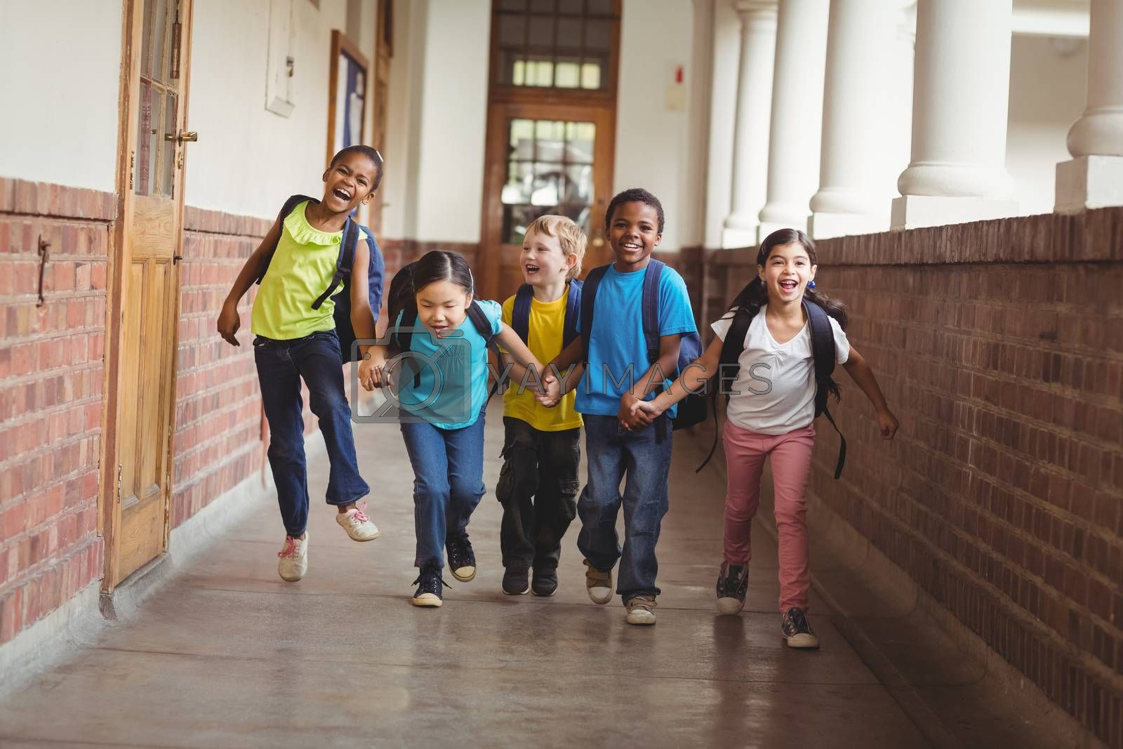 Happy pupils holding hands and running at corridor in school