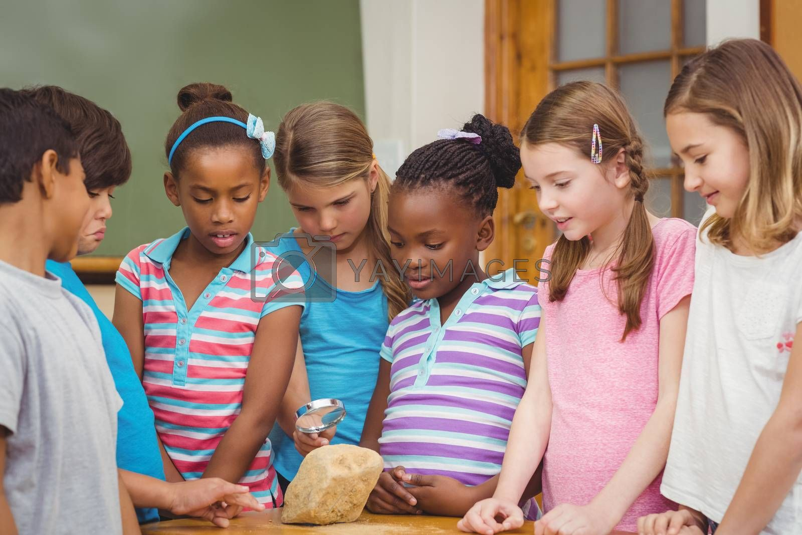 Pupils looking at rock with magnifying glass at the elementary school