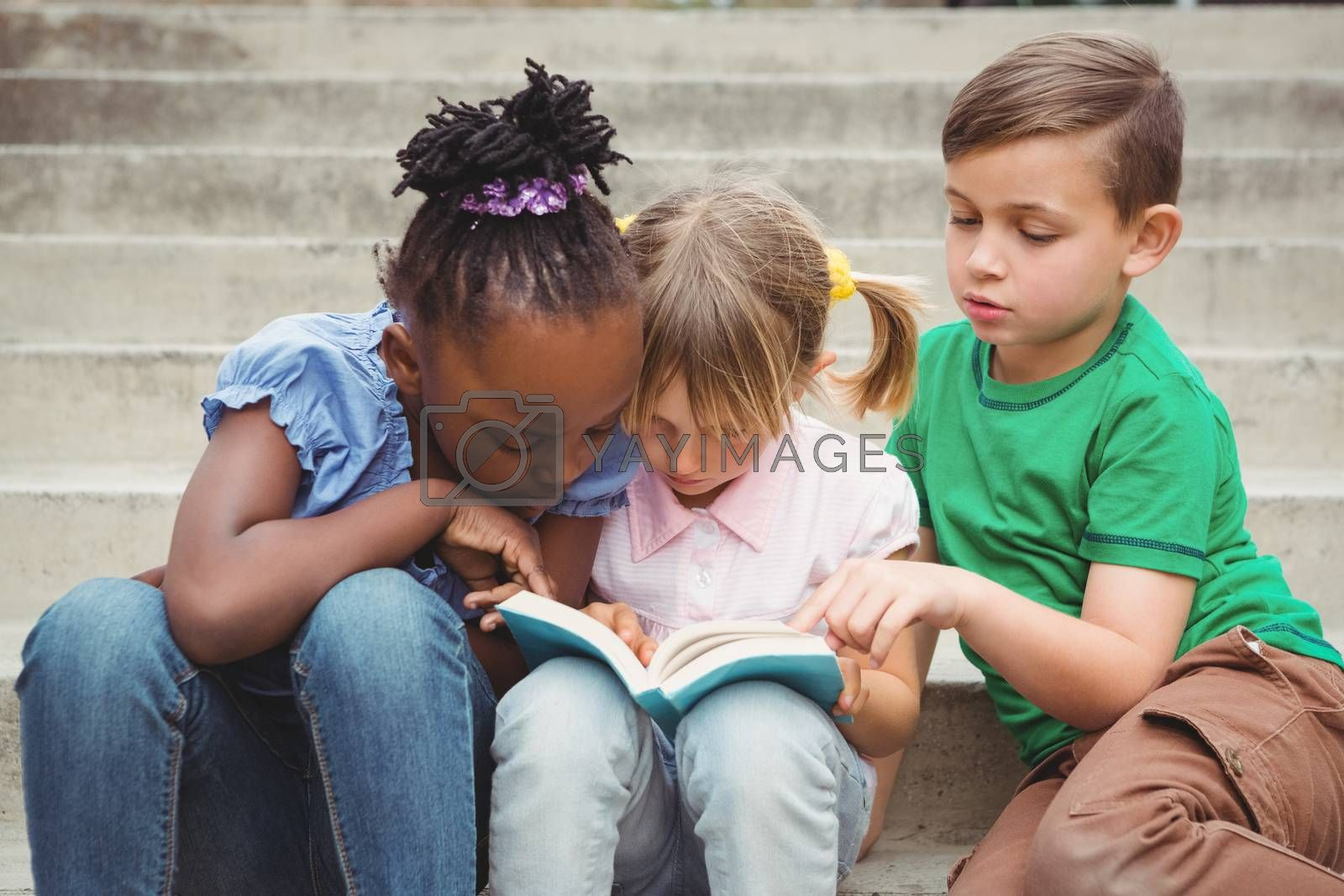 Students sitting on steps and reading a book on the elementary school grounds