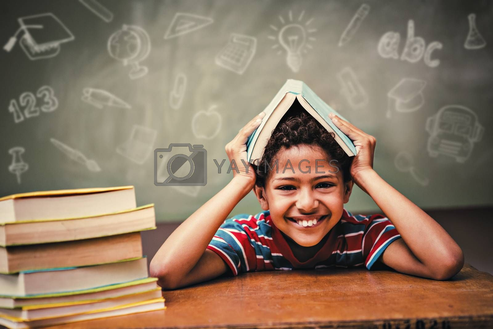 Education doodles against little boy holding book over head in classroom