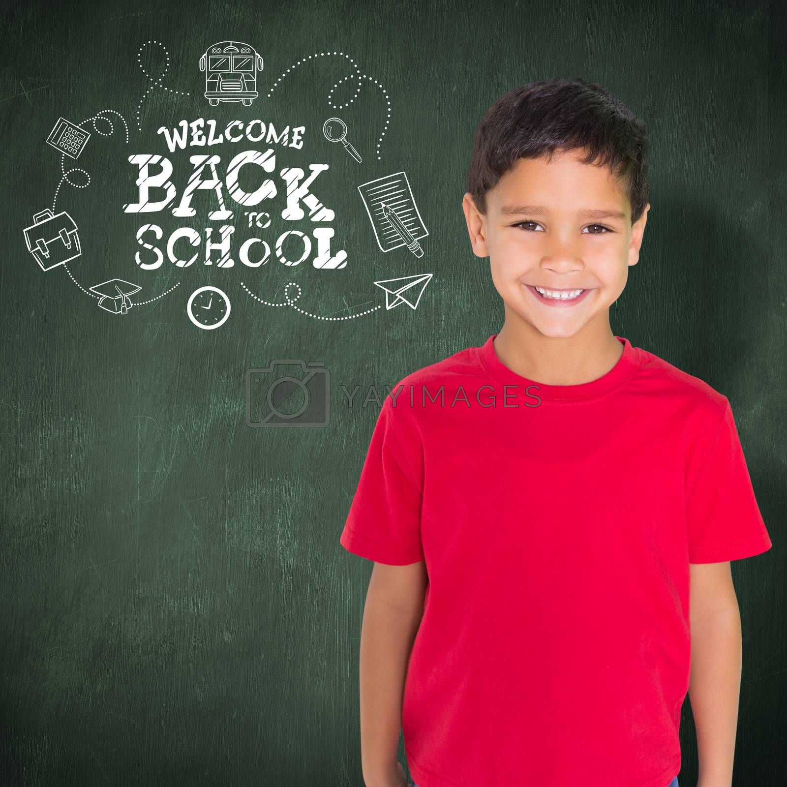 Cute boy smiling at camera against green chalkboard