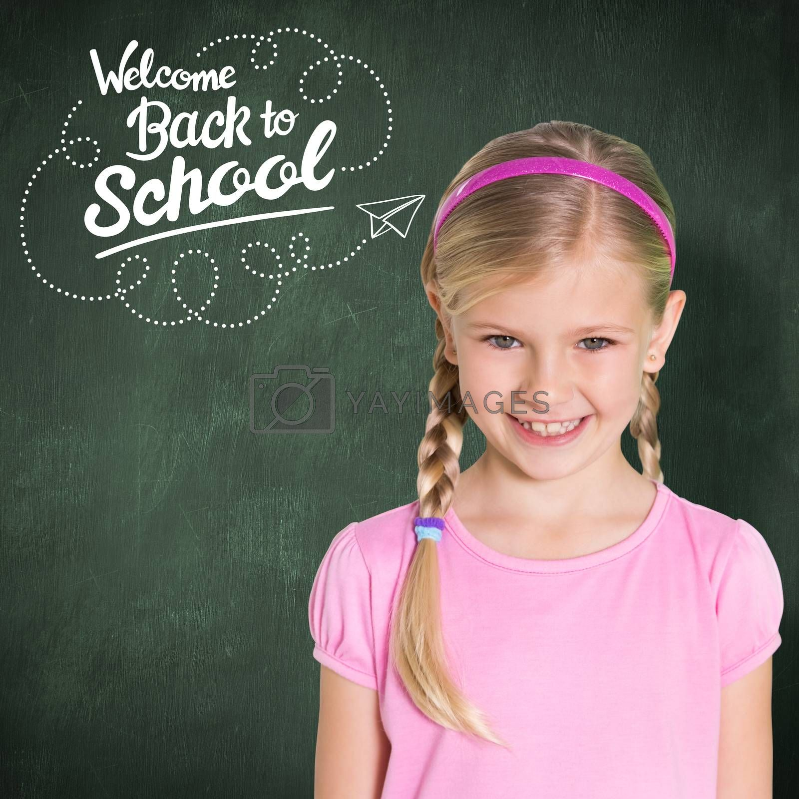Cute girl smiling at camera against green chalkboard