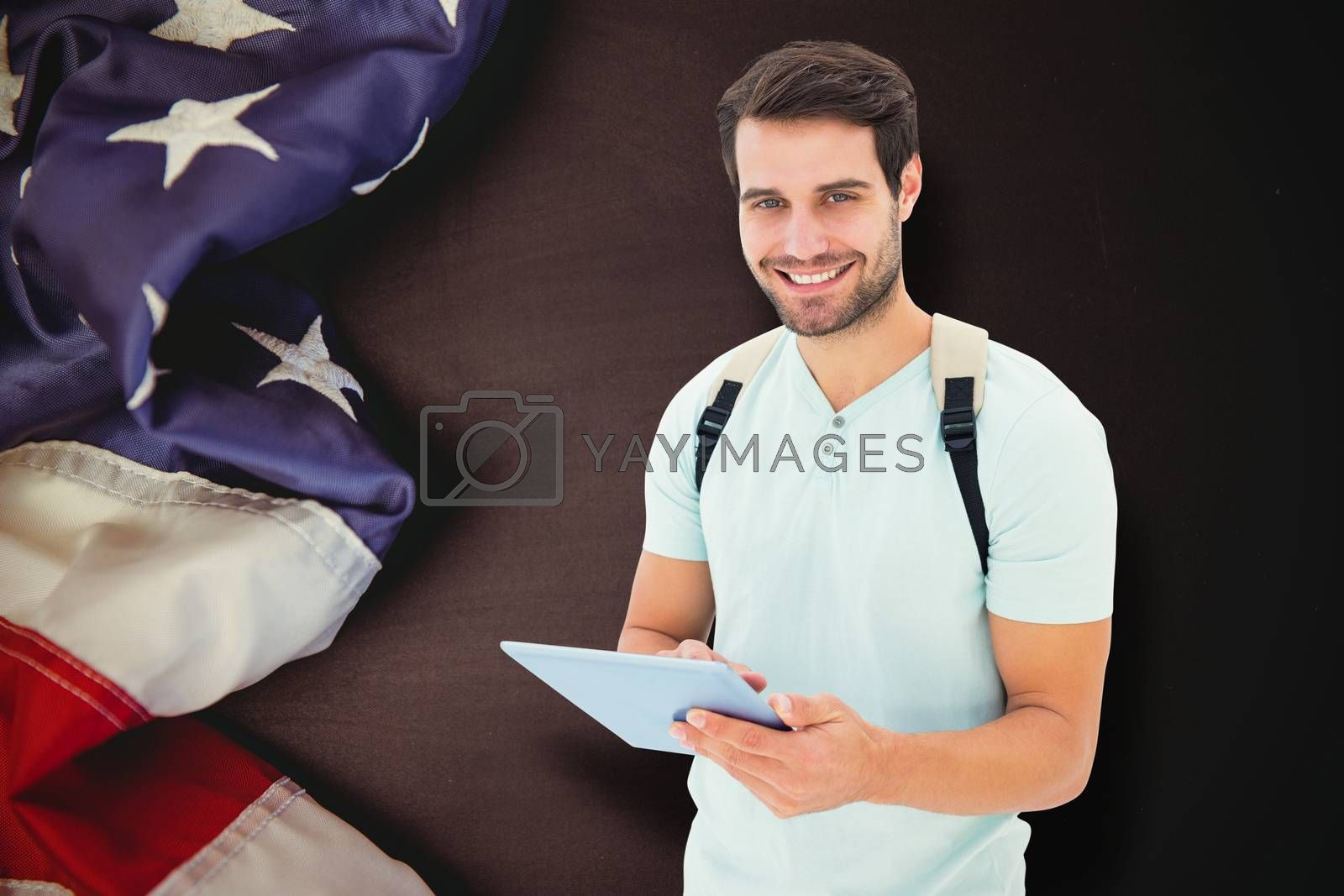 Student using tablet pc against american flag on chalkboard