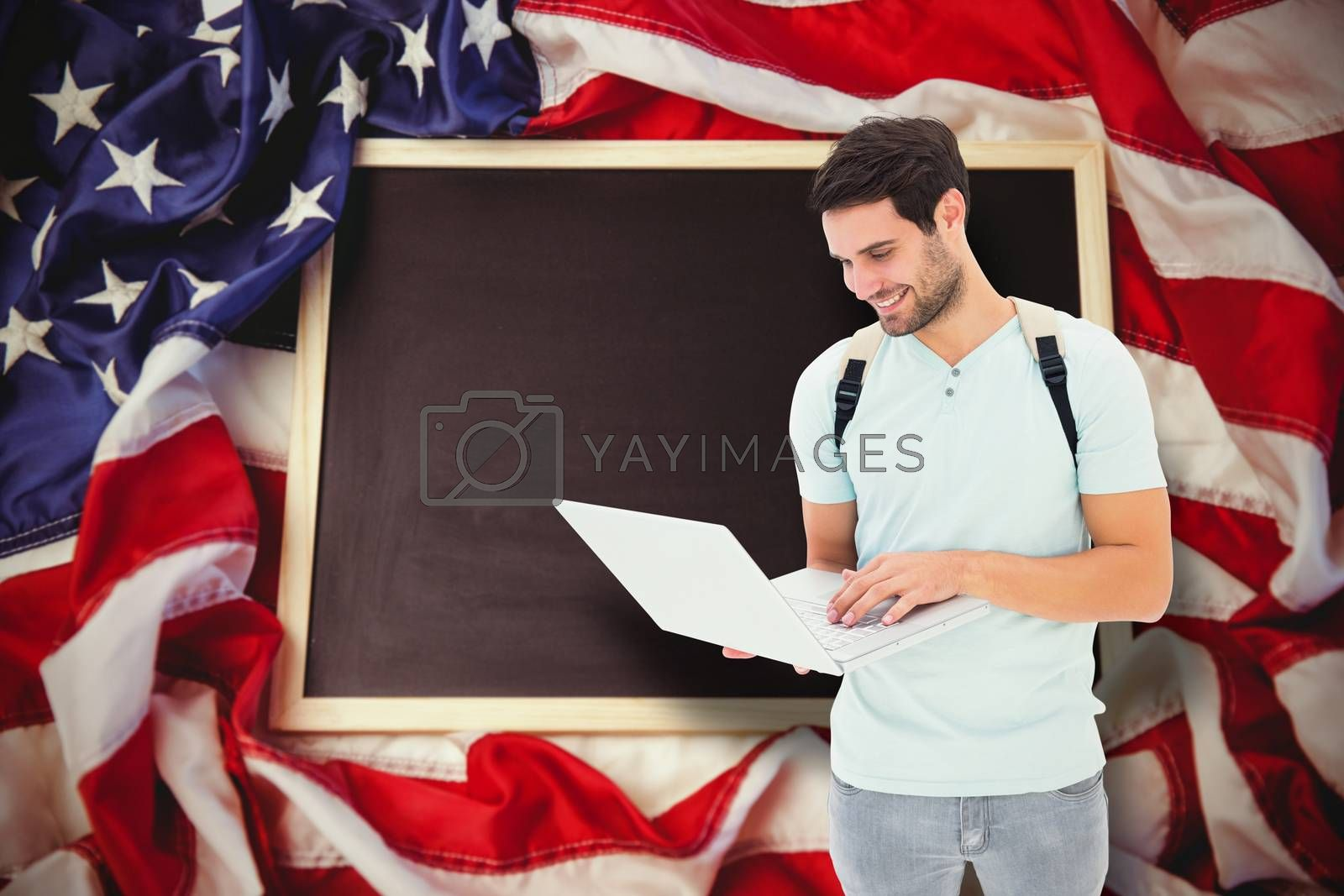 Student using laptop against american flag on chalkboard