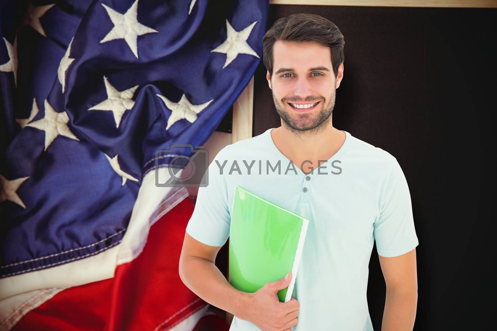 Student holding notepad against american flag on chalkboard