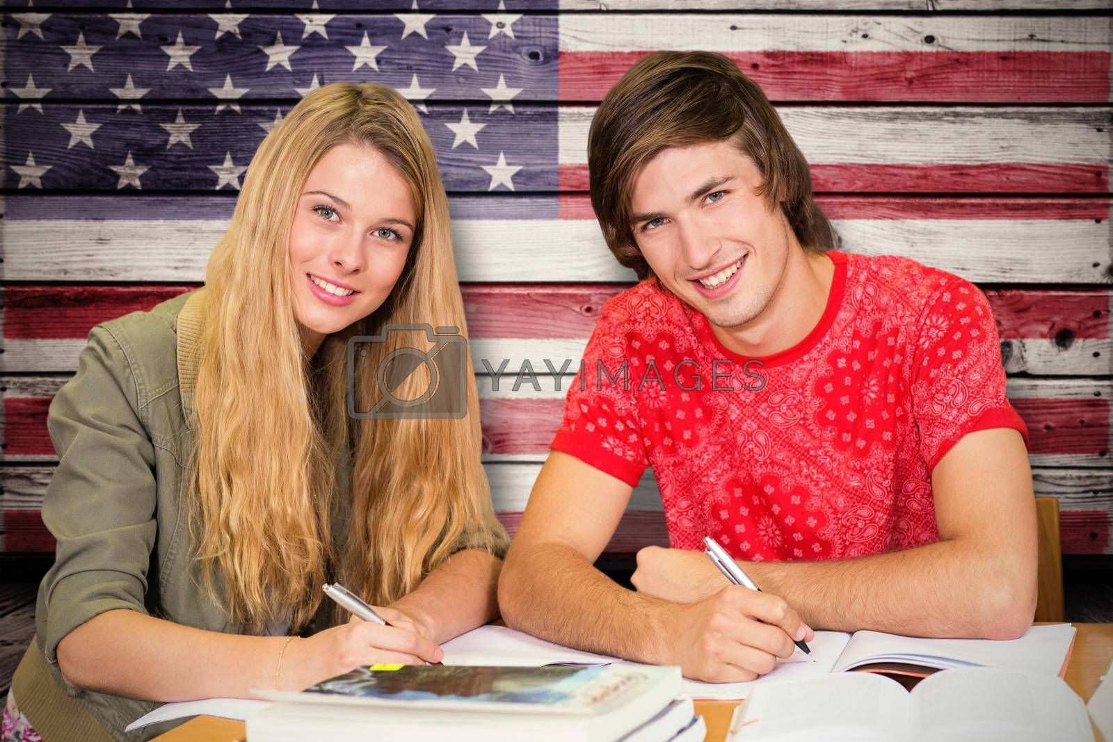 Students studying against composite image of usa national flag