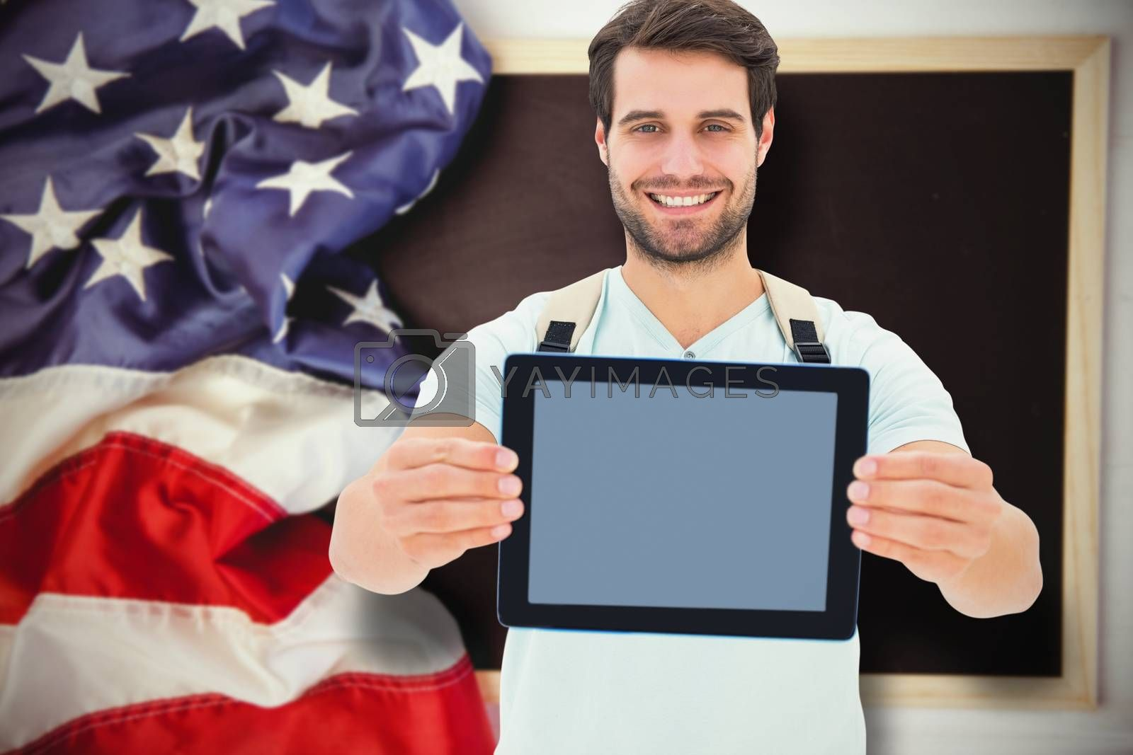 Student showing tablet against american flag on chalkboard