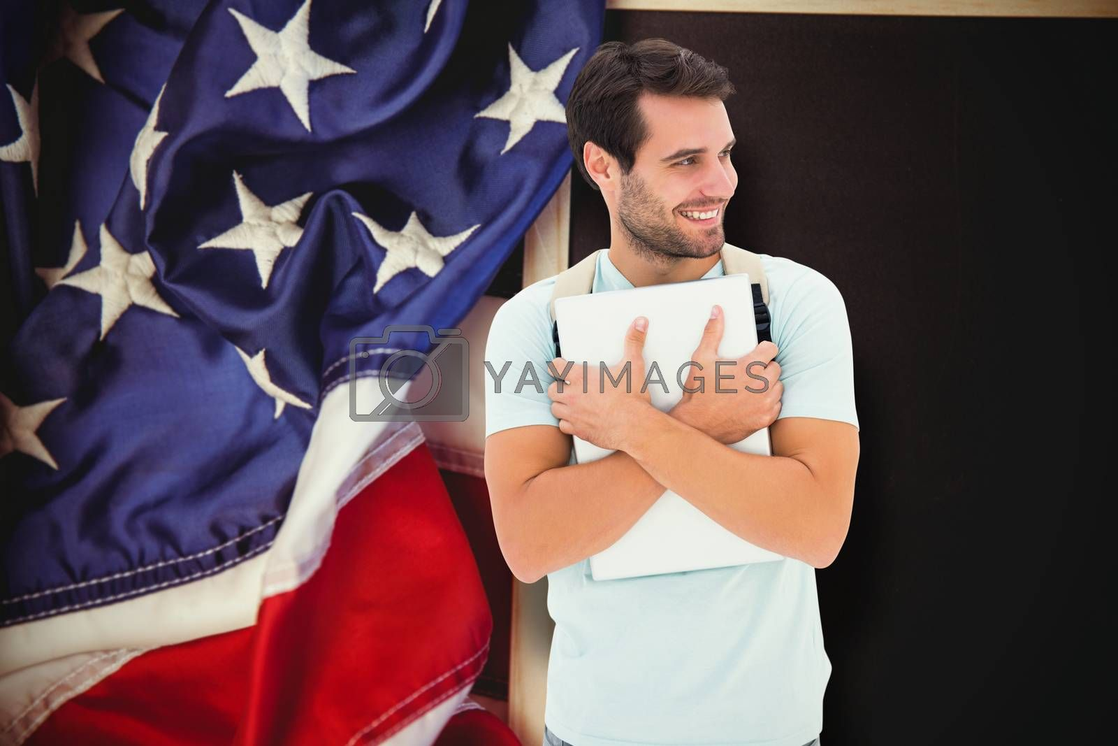 Student holding laptop against american flag on chalkboard