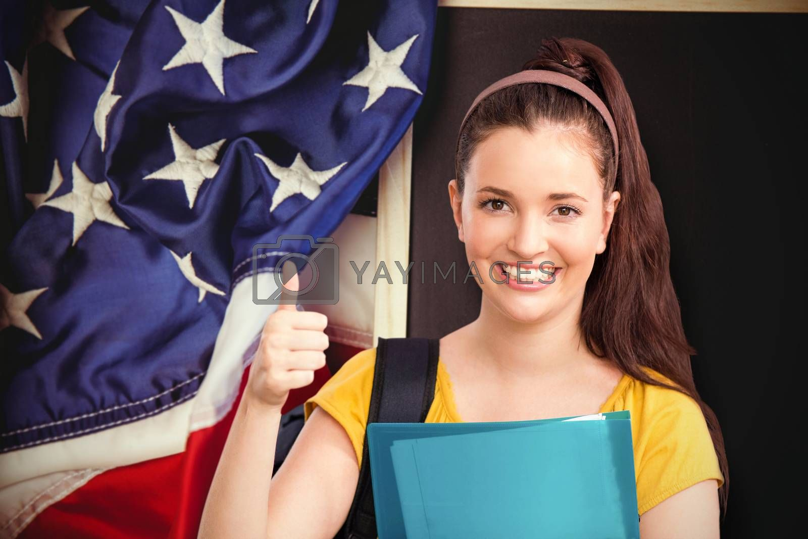 Student with thumbs up against american flag on chalkboard