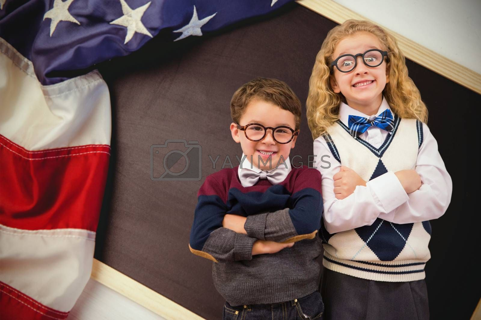 Cute pupils looking at camera against american flag on chalkboard