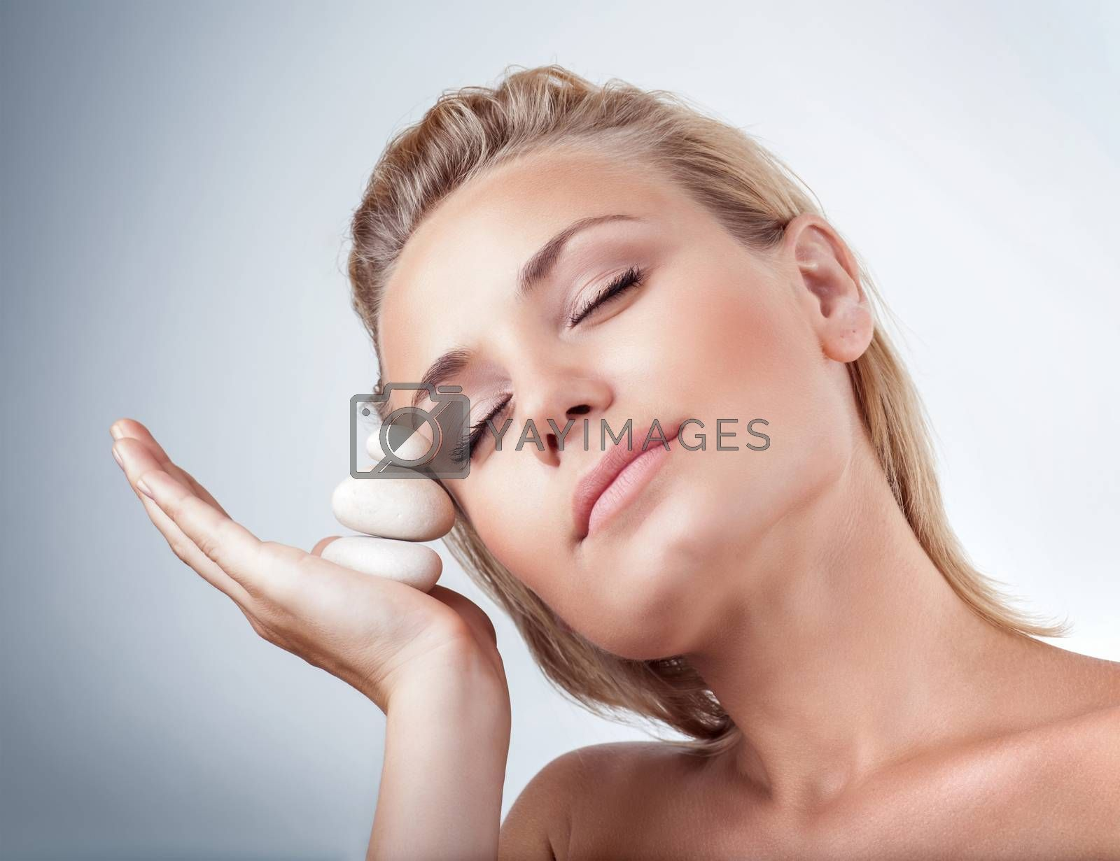 Portrait of gentle female with closed eyes holding on hand spa stones over gray background, healthy lifestyle, beauty and spa salon