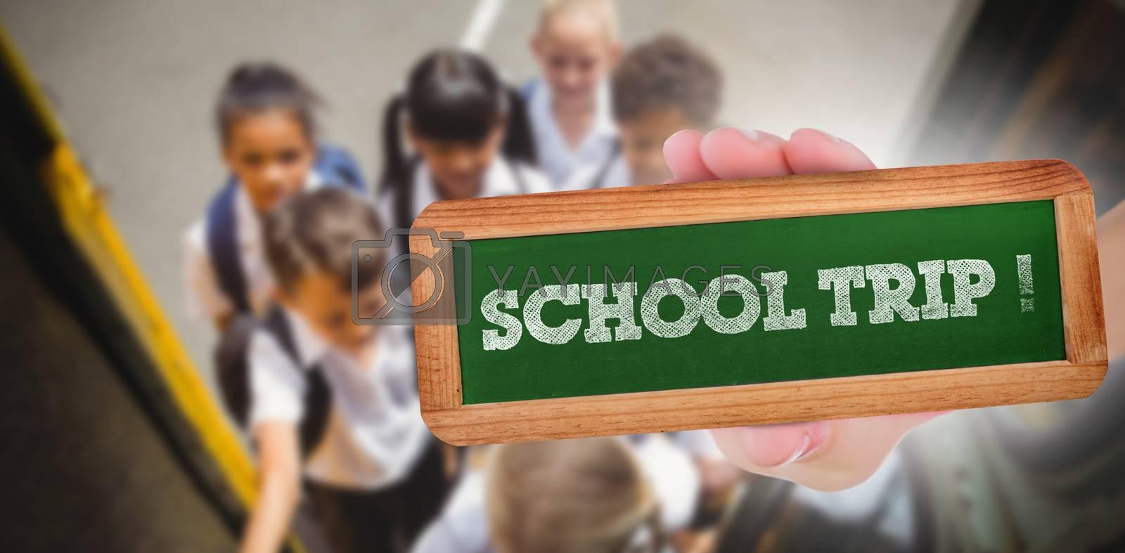 The word school trip! and hand showing chalkboard against cute schoolchildren getting on school bus