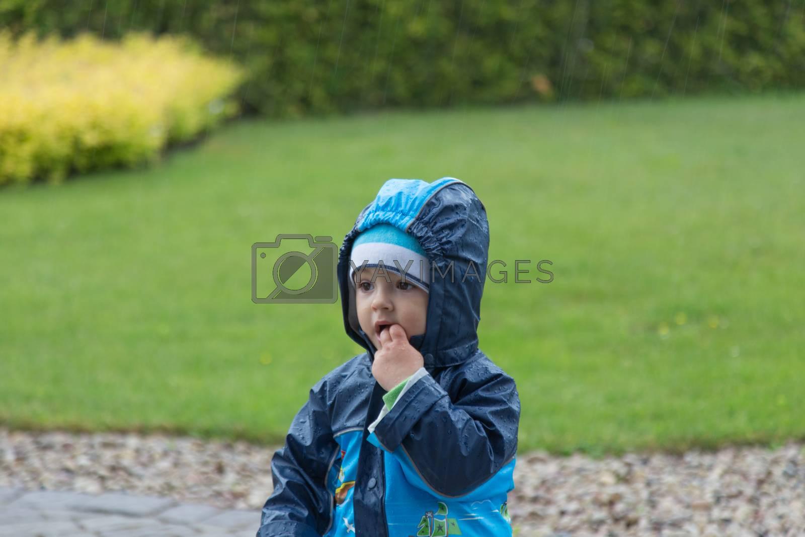 pretty little baby boy under rain