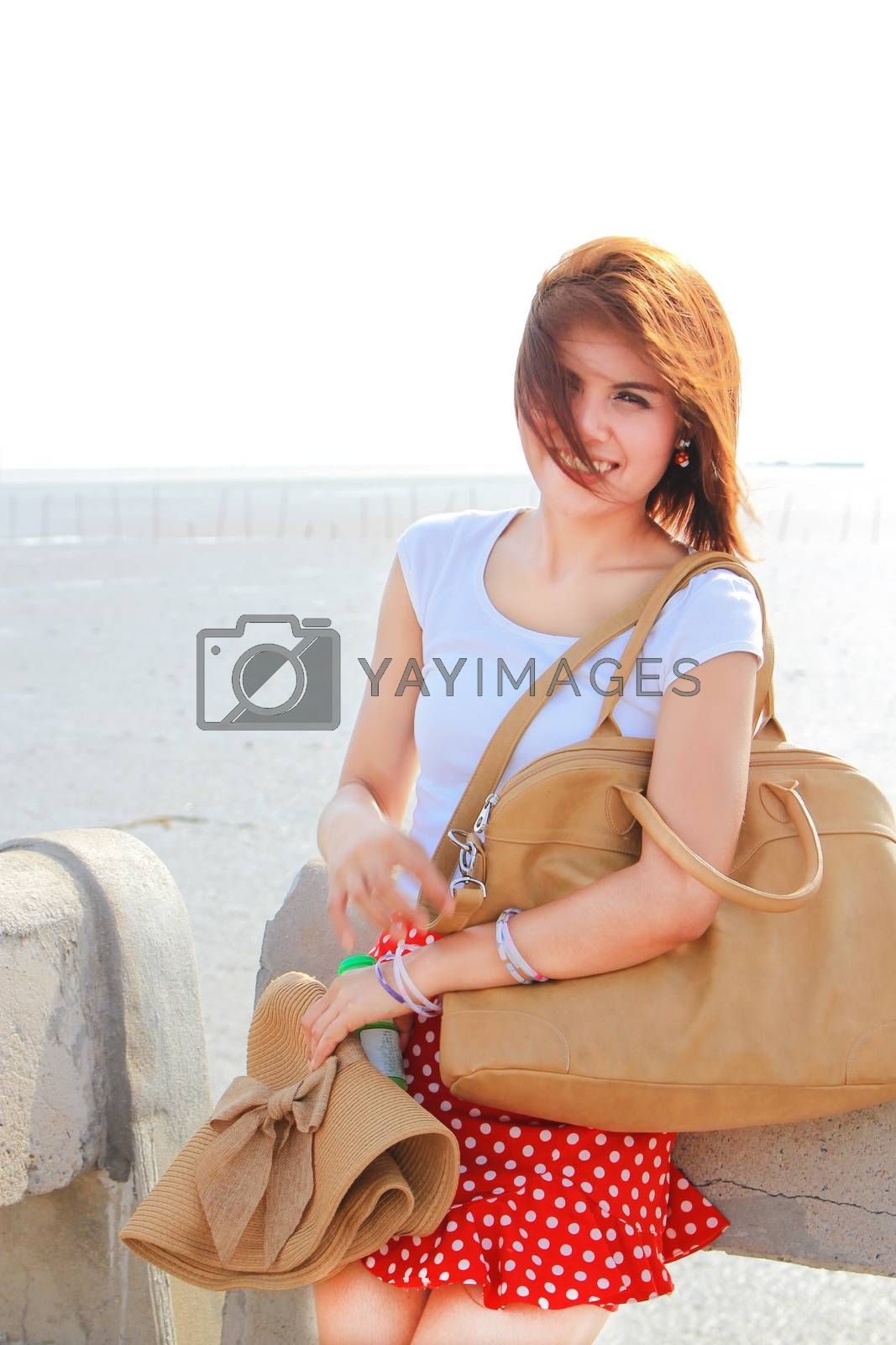 Happy lady at the beach with her brown hat and leather bag
