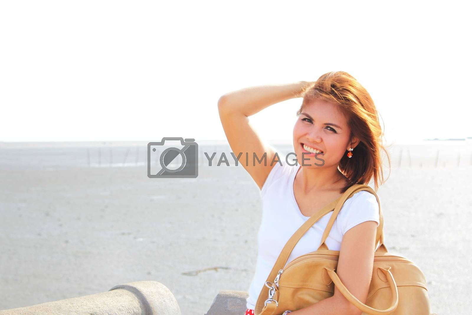 Happy lady at the beach with her brown leather bag