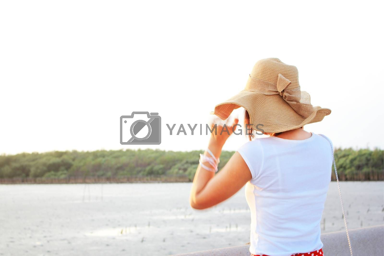 Lady at the beach with her brown hat