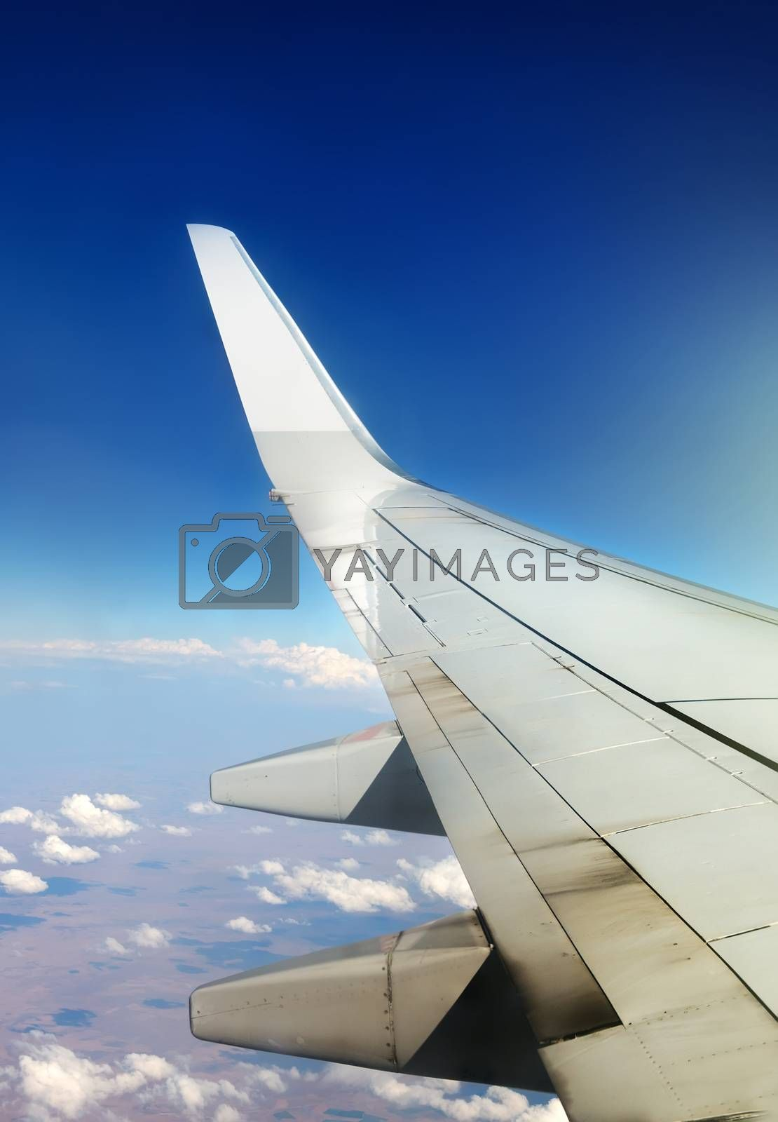 Wing of plane in sky and white clouds