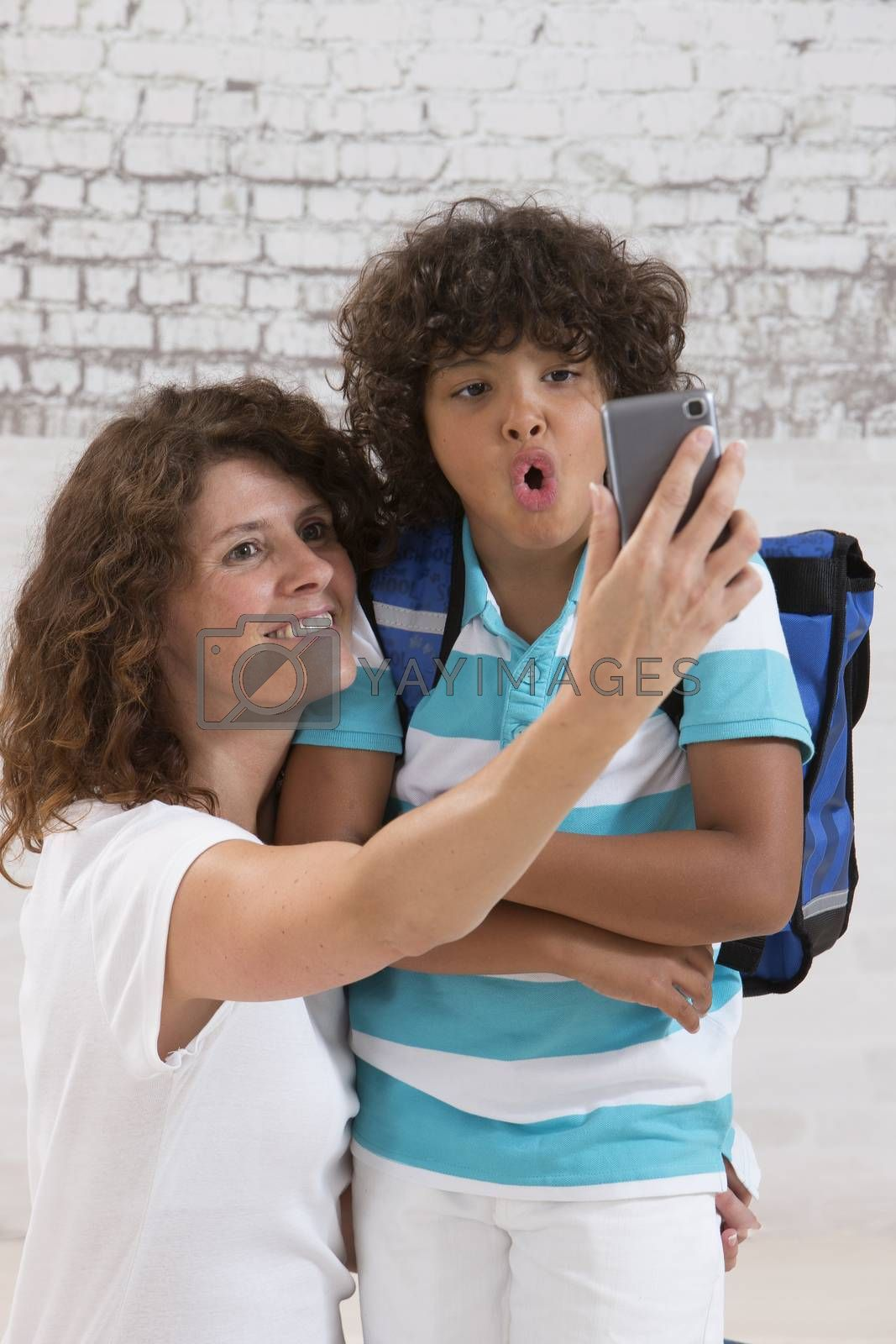 mother and sun are doing selfie by mobile phone before first day of school